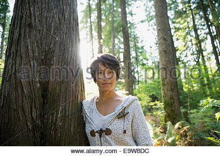 Portrait of confident woman leaning against tree - Stock Photo
