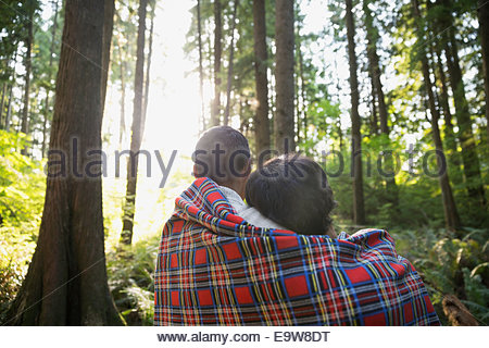 Couple wrapped in blanket in woods - Stock Photo