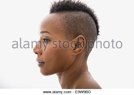 Close up profile of serious woman with mohawk - Stock Photo