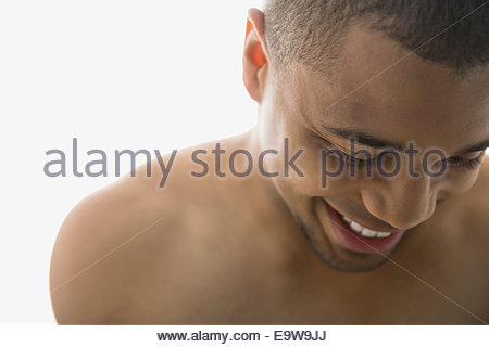 Close up of bare chested man looking down - Stock Photo