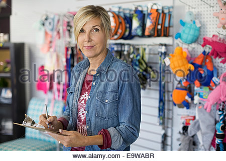 Portrait of dog daycare owner checking inventory - Stock Photo