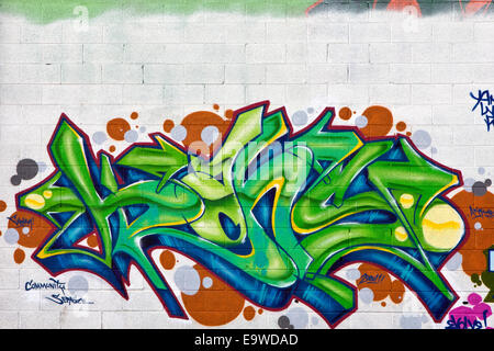 A colorful green, blue, and orange graffiti painting on a white brick wall - Stock Photo