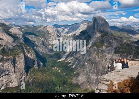 Yosemite National Park with tourists at Glacier Point overlook viewing Half Dome at right. - Stock Photo