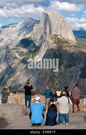 Yosemite National Park with tourists at Glacier Point overlook viewing Half Dome. - Stock Photo