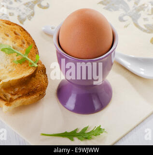 Boiled brown egg in eggcup. Selective focus - Stock Photo