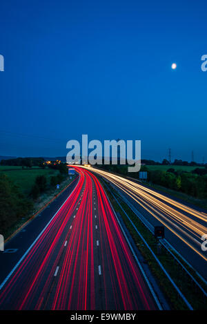 Full moon and light-trails of traffic on the M6 near Lancaster (Forton) services Lancashire - Stock Photo