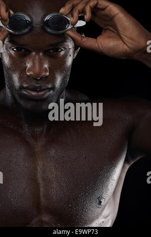 Close-up image of young male swimmer with goggles. African man with swimming glasses against black background. - Stock Photo