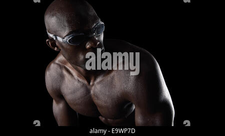 Studio shot of African male swimmer wearing goggles looking over shoulder against black background. Muscular young - Stock Photo