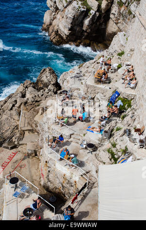 Tourists relax, sunbathe and swim along the base of the city walls in Dubrovnik Old Town, Croatia. - Stock Photo