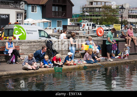 Families with children crabbing at the harbour at Lymington - Stock Photo