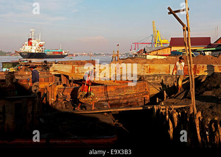 Workers uploading sands from a barge while a cargo ship passes through the Musi River in South Sumatra, Indonesia. - Stock Photo