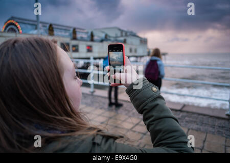Aberystwyth Wales UK, Monday 3rd November 2014  A girl photographs her friends on her mobile phone as cold windy - Stock Photo