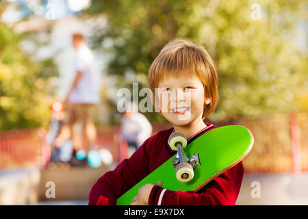 Close-up view of smiling boy with green skateboard - Stock Photo