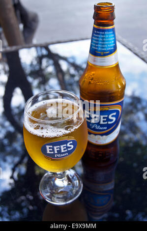 A glass and bottle of Efes Turkish beer,  Bodrum, Turkey, pub table drinks glasses - Stock Photo