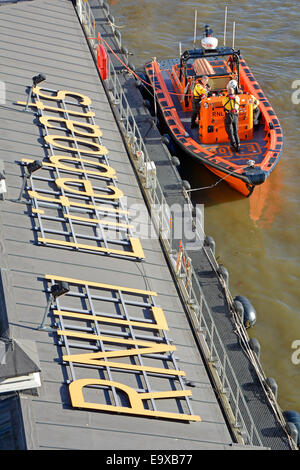 RNLI station on River Thames beside The Victoria Embankment with crew on standby in lifeboat - Stock Photo