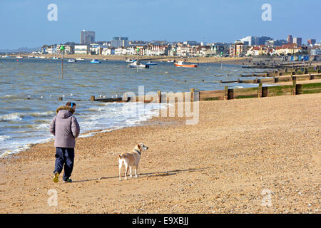 Walking the dog on a cold windy February day beside the Thames Estuary - Stock Photo