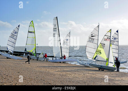 Preparing to launch sailing dinghies into the Thames Estuary from Shoeburyness beach on a cold windy February day - Stock Photo