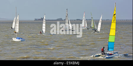 Sailing dinghies in the Thames Estuary with Southend on Sea pier beyond on a cold windy February day - Stock Photo