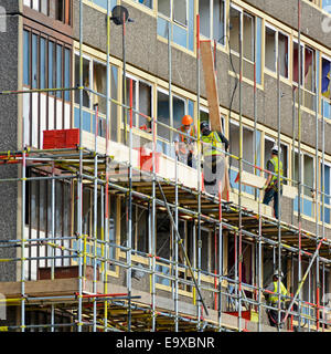 Scaffolders working on one of the empty Heygate Estate high rise social housing blocks in preparation for regeneration - Stock Photo