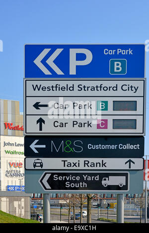 Westfield shopping centre at Stratford City showing car park sign with store signs beyond - Stock Photo