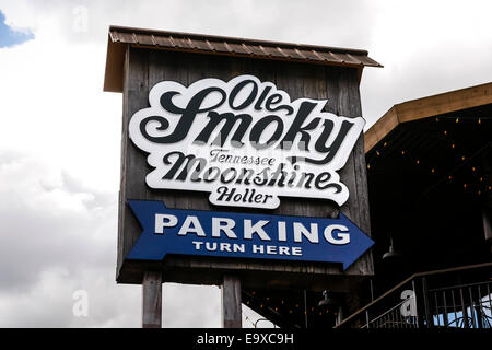 Overhead sign pointing to the Ole Smoky Tennessee Moonshine Holler and Parking in Gatlinburg TN - Stock Photo