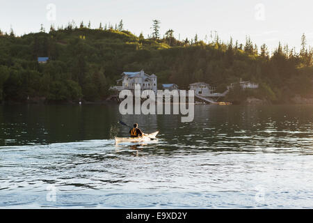 Sea Kayaker paddling at sunset in Halibut Cove, Kachemak Bay, Southcentral Alaska. - Stock Photo