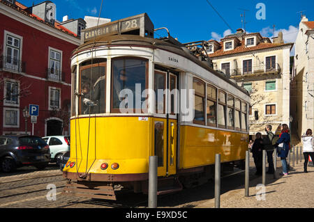Horizontal streetview of the traditional yellow tram in Lisbon. - Stock Photo