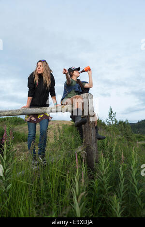 Two women sitting on a wooden fence above Halibut Cove, Kachemak Bay, Southcentral Alaska. - Stock Photo