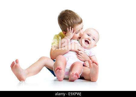 Boy kissing his little sister baby isolated on white - Stock Photo