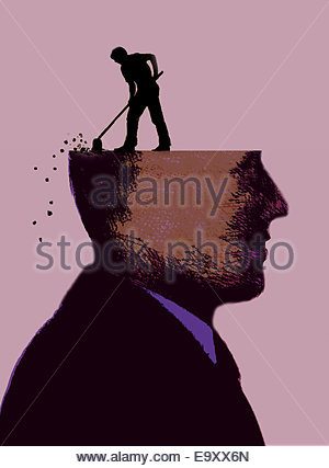 Man clearing debris from head of businessman - Stock Photo