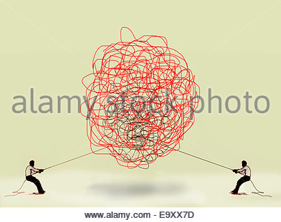 Two men pulling at tangled rope in opposite directions - Stock Photo