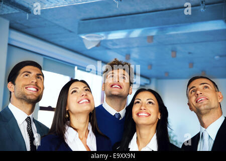 Happy positive business group looking up with dreaming expression - Stock Photo