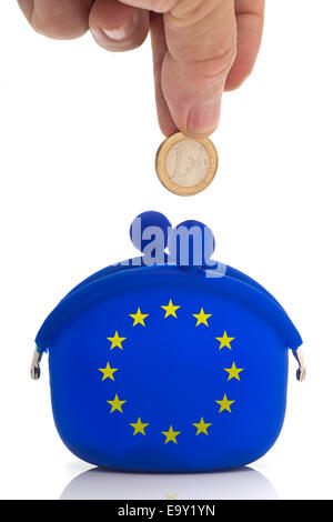 Hand dropping a euro coin in a blue purse with euro-stars - Stock Photo