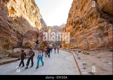 Tourists are walking through 'the Siq'.'The Siq' is a narrow gorge who leads visitors into Petra in Jordan - Stock Photo