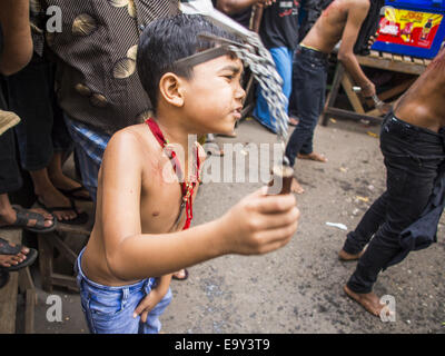 Yangon, Yangon Division, Myanmar. 4th Nov, 2014. A Burmese boy flagellates himself with chains and razors in front - Stock Photo