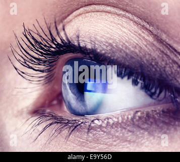 Closeup of a young woman eye with blue computer screen reflection in it - Stock Photo
