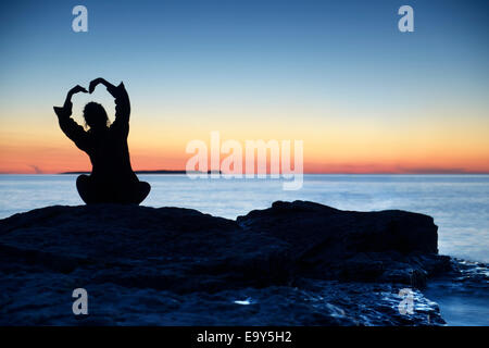 Silhouette of a woman sitting alone an a shore at sunset with her hands raise in a shape of a flower above her head, - Stock Photo