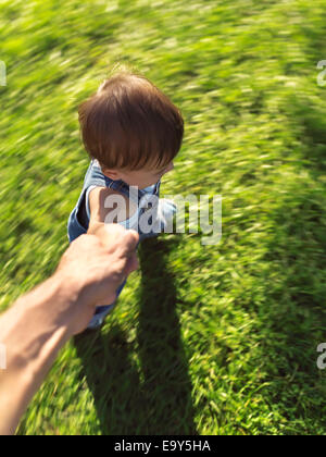 One year old child running on the grass holding his father's hand, artistic dynamic photo with motion blur. - Stock Photo