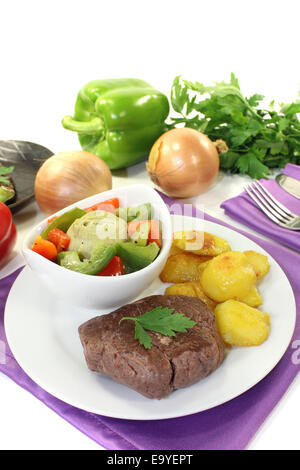 Ostrich steaks with baked potatoes and vegetables on bright background - Stock Photo