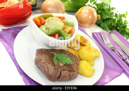 Ostrich steaks with baked potatoes on bright background - Stock Photo