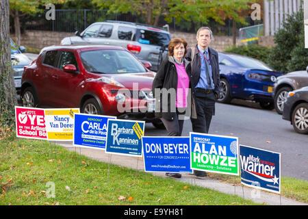 Arlington, Virginia, USA. 4th November, 2014. Couple walks by signs to polls for voting November 4, 2014. Lyon Village - Stock Photo