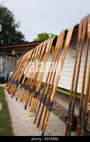 Many oars leaning against the side of the clubhouse - Stock Photo