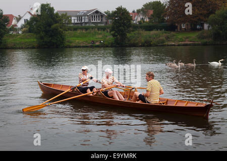 Rowing club members set off in their skiff on the thames - Stock Photo