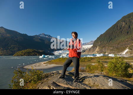 Caucasian middle age male holding a camera and standing in front of Mendenhall glacier near Juneau, Southeast Alaska, - Stock Photo