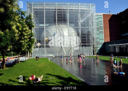 NYC:  Children playing in the Arthur Ross Terrace water fountains next to the Hayden Planetarium - Stock Photo