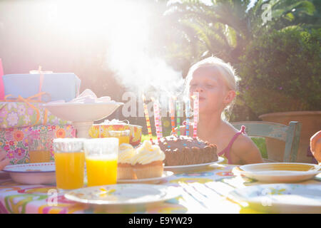 Girls blowing out candles on birthday cake - Stock Photo