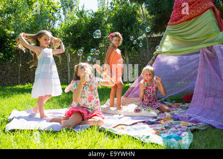 Girls blowing bubbles in summer garden party - Stock Photo