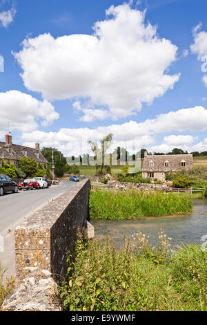 The Swan Inn on the banks of the River Windrush in the Cotswold village of Swinbrook, Oxfordshire UK - Stock Photo