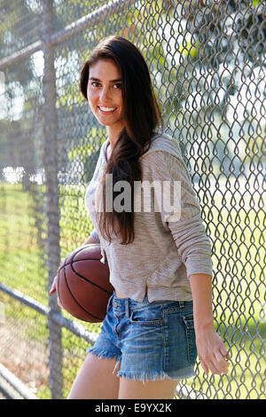 Young woman with basketball standing by wire fence - Stock Photo