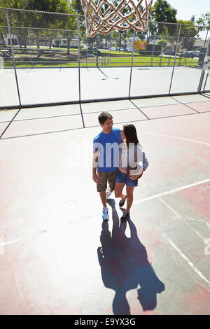 Young couple hugging in basketball court - Stock Photo